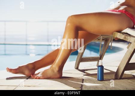 Las hembras jóvenes relajándose en un sillón con un bronceado spray por la piscina. Señorita de sol junto a la piscina.