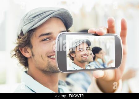 Imagen compuesta de mano sujetando el smartphone mostrar