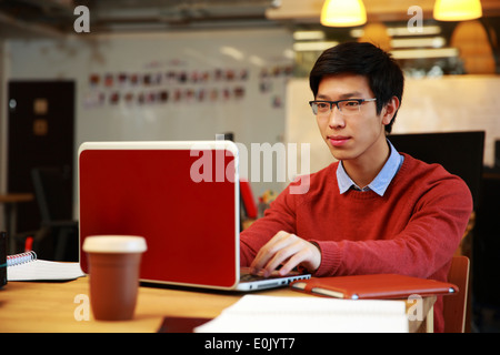 Apuesto hombre asiático en vidrios trabajando en el portátil en la oficina