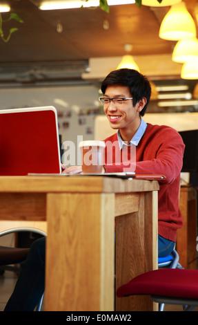 Sonriente hombre asiático en vidrios trabajando en el portátil