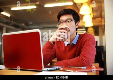 Apuesto hombre asiático trabajando en el portátil y bebiendo café