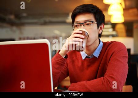 Joven asiático hombre trabajando con un portátil y bebiendo café