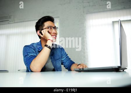Feliz hombre asiático sentado en su lugar de trabajo en la oficina y hablar por teléfono
