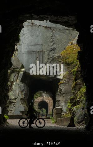 Ciclista dentro de uno de los túneles, Othello Coquihalla Provincial Park, KVR Trail, Trans-Canada Trail, British Columbia, Canadá Foto de stock