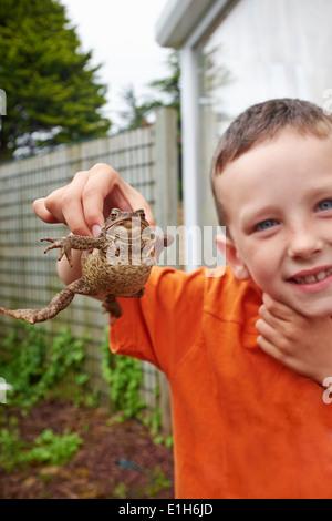 Retrato de niño en el jardín mantiene sapo