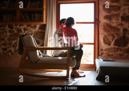 Mitad hombre adulto e hija mirando afuera de la ventana