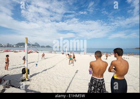 RIO DE JANEIRO, Brasil - Enero 2011: jóvenes brasileños ver un juego de footvolley, un deporte de fútbol y voleibol.