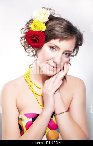 Bella mujer - equinoccio feliz muchacha con flores posando en el studio