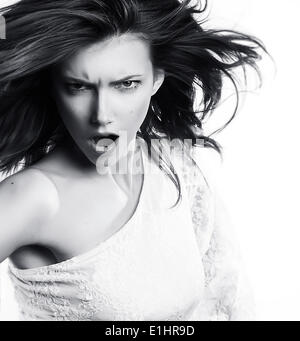 Mujer joven gritando sobre fondo blanco - foto en blanco y negro