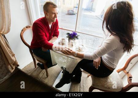 La longitud completa de la pareja romántica cogidos de la mano en el café