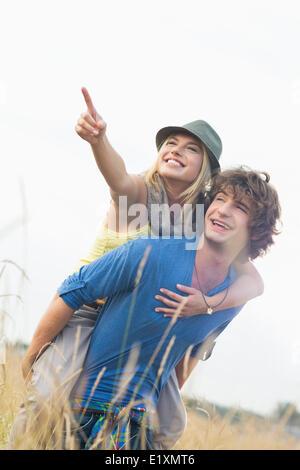 Mujer alegre mostrando algo mientras disfruta piggyback ride sobre el hombre en el campo