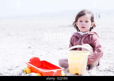 Niña jugando en la arena en la playa.
