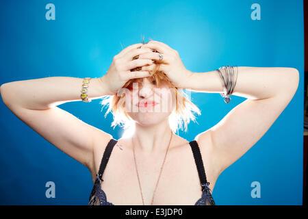Mujer joven con las manos en la cabeza gesticulaciones