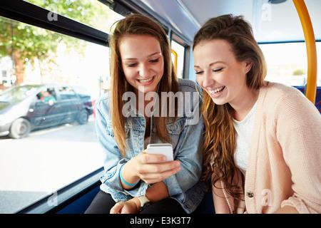 Dos mujeres jóvenes, la lectura de un mensaje de texto en el bus Foto de stock