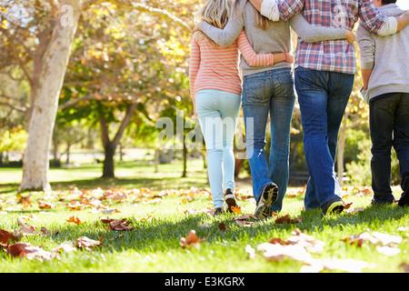 Vista trasera de la familia caminando a través del bosque de Otoño