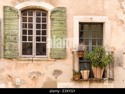 Detalle de la pared de una casa en un pueblo provenzal. Ventana, balcón y pared de estuco rugoso. Típica casa de Foto de stock