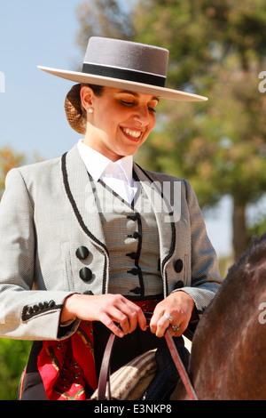 Jinete femenino decorados en el tradicional sombrero rematado sentado en su caballo sonriente durante la Feria del Caballon, Españas feria del caballo Foto de stock