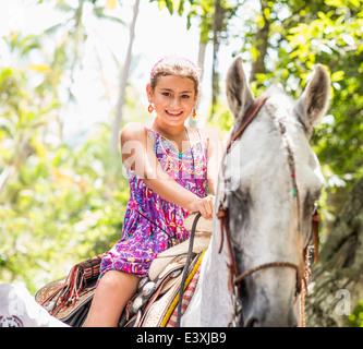 Niña de raza mixta en caballo en la selva