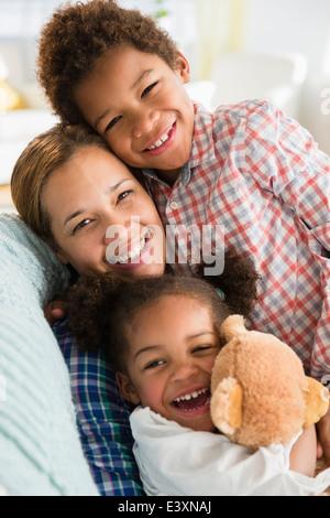 Madre Negra y niños sonrientes en el sofá Foto de stock