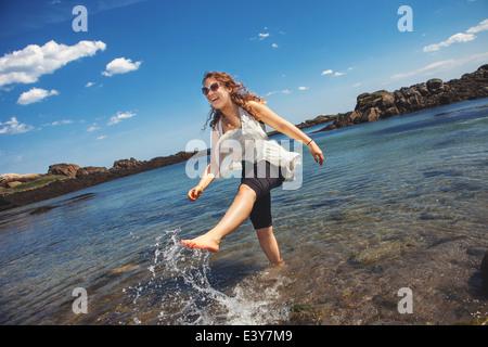 Mujer joven en el mar, en la playa rocosa costera en Biddeford, Maine, EE.UU.