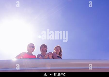 Retrato de tres amigos adultos mirando hacia abajo desde el yate