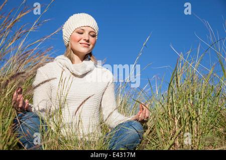 Mujer joven en posición de loto del yoga en el césped largo
