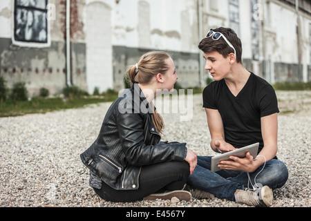 La pareja de adolescentes conversando sobre tableta digital Foto de stock