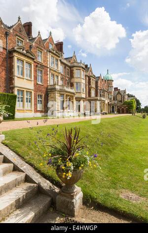 Casa de Sandringham, una casa de campo, el Queen's Norfolk Retreat, en verano con un cielo azul y nubes blancas mullidas