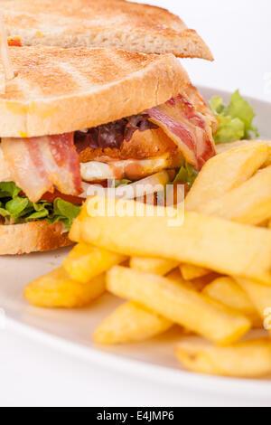 Deliciosa carne en rodajas delgadas pastrami sándwich club con lechuga rizada frescos servidos con un pequeño plato de verduras encurtidas en una