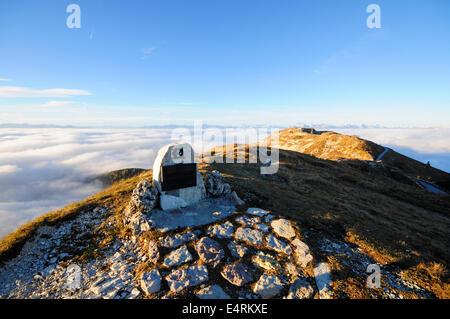 Monumento militar en la cima de una montaña con una luz que emerge de las nubes