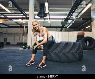 Mujer sentada en el neumático y sonriendo a la cámara en el gimnasio. Crossfit atleta femenina teniendo descanso después del trabajo.