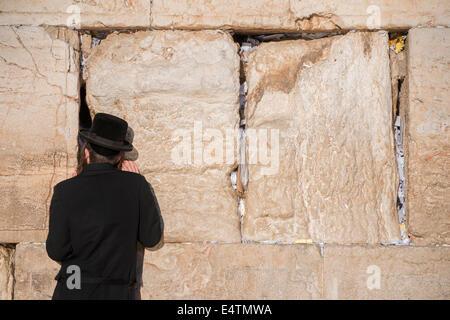 Hombre judío reza junto a una grieta llena de cartas que contenían oraciones escritas en el Muro Occidental en Jerusalén. Israel