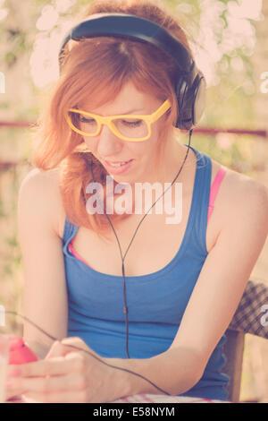 Hermosa chica hipster con grandes auriculares escuchando la música en su teléfono inteligente rosa. Colores retro, Destello de lente Foto de stock