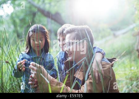Los alumnos y el profesor examinando la hierba en el bosque Foto de stock