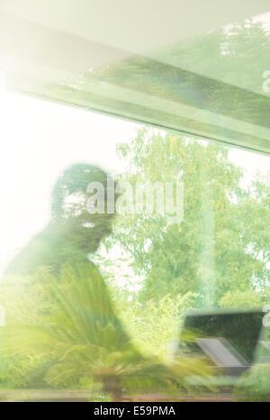 Hombre utilizando laptop vistos a través de la ventana