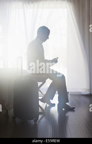 Empresario con teléfono móvil en la habitación del hotel