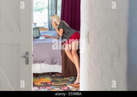 Mujer hablando por teléfono celular en el dormitorio Foto de stock