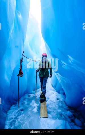 Mujer de pie en una cueva de hielo, el glaciar Fox, Westland Tai Poutini National Park, Isla del Sur, Nueva Zelanda, el Pacífico