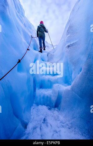 Mujer caminando pasos fuera de una cueva de hielo en el glaciar Fox, Westland Tai Poutini National Park, Isla del Sur, Nueva Zelanda, el Pacífico