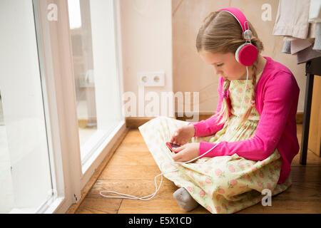 Chica sentada en el suelo Seleccionar música para auriculares