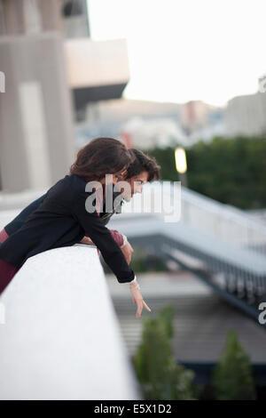 Pareja mirando hacia abajo y apuntando desde la azotea de la ciudad