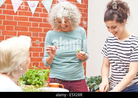 Tres mujeres preparando comida fresca a mesa de jardín