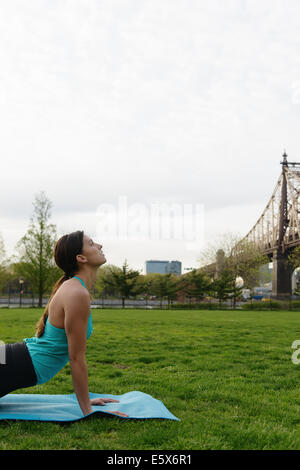 Mujer joven practicando yoga en el parque de la ciudad