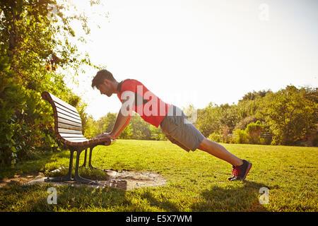 Macho joven corredor haciendo flexiones sobre un banco del parque Foto de stock