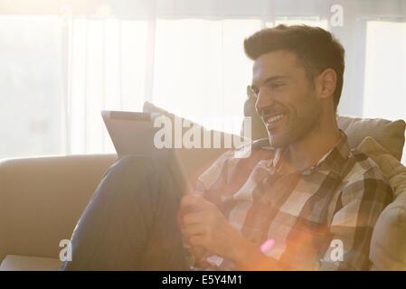 Hombre sentado con ventana, utilizando tablet digital