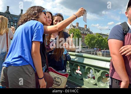 Londres, Inglaterra, Reino Unido. Tres jóvenes mujeres en Westminster Bridge teniendo un selfie con un teléfono móvil