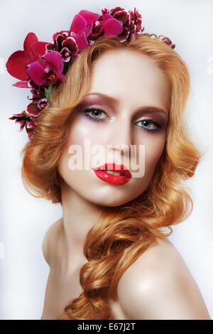 Exquisita Auburn mujer con corona de flores y árboles Foto de stock