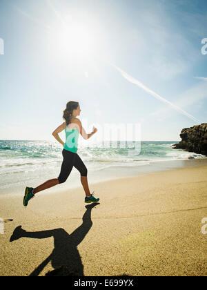 Mujer caucásica ejecutando en la playa