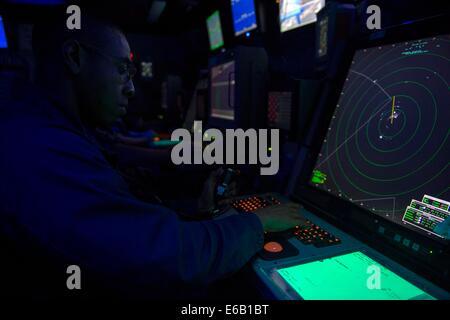 Marina de primera clase de controlador de Tránsito Aéreo Fernando Montes significa ver control de aproximación en el centro de control de tráfico aéreo de anfibio a bordo del buque de asalto anfibio de encargo USS América (LHA 6) en el Océano Atlántico, el 31 de julio de 2014. Las Américas