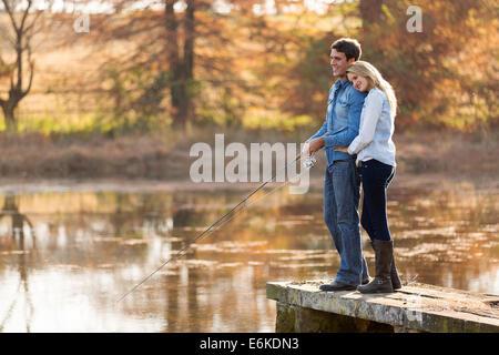 Adorable joven pareja junto a un lago de pesca